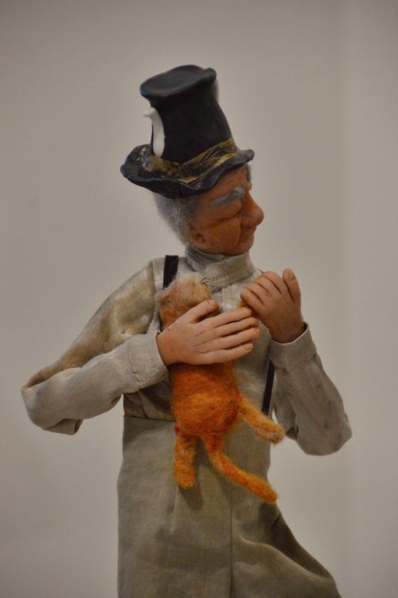 Title : Cat and Tea  Description : Art doll /mixed media sculpture, inspired by the Edward Lear limerick :     There was an old man on the Border, Who lived in the utmost disorder;  He danced with the cat, and made tea in his hat,  Which vexed all the folks on the Border.  Techniques :  •Machine and handstitched clothing   • Tea dyed fabrics  •Sculpted  polymer clay head, hands and feet, •	Wrapped wire armature   •	 Needle felting (cat)   Materials : Tea dyed  fabrics, tea bag paper, wool fabric, wool roving, stretch cotton fabric , polymer clay aluminium wire and foil, aluminium tea pot and china miniature.