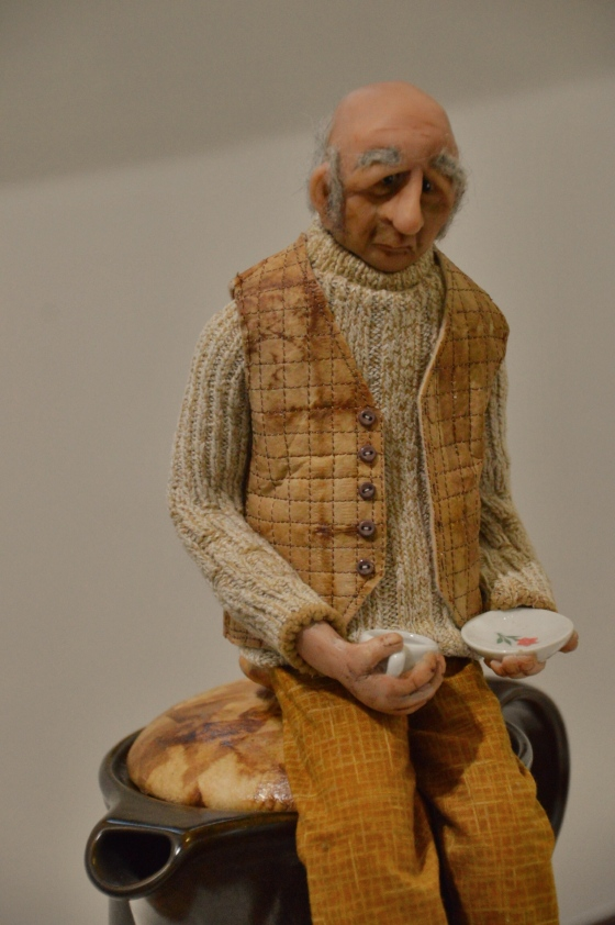 Title : Camomile Tea  Description : Art doll /mixed media sculpture, inspired by the Edward Lear limerick :  There was an Old Man of Vienna, Who lived upon Tincture of Senna; When that did not agree, He took Camomile Tea, That nasty Old Man of Vienna.  Techniques :  • Machine and handstitched clothing - vest created from tea bag paper attached to wool fabric and machine stitched in a grid pattern •Fabrics overdyed with tea •	Sculpted  polymer clay head, hands and feet, •	Wrapped wire armature   •	Decoupage with tea bags  Materials : Upcycled tea dipped  fabrics, tea bag paper, wool fabric, wool roving, stretch cotton fabric , polymer clay aluminium wire and foil, china tea pot and miniatures.